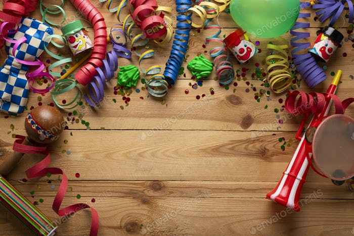Carnival background on a wooden surface. Masks, balloons, coiled streamers, confetti and many more