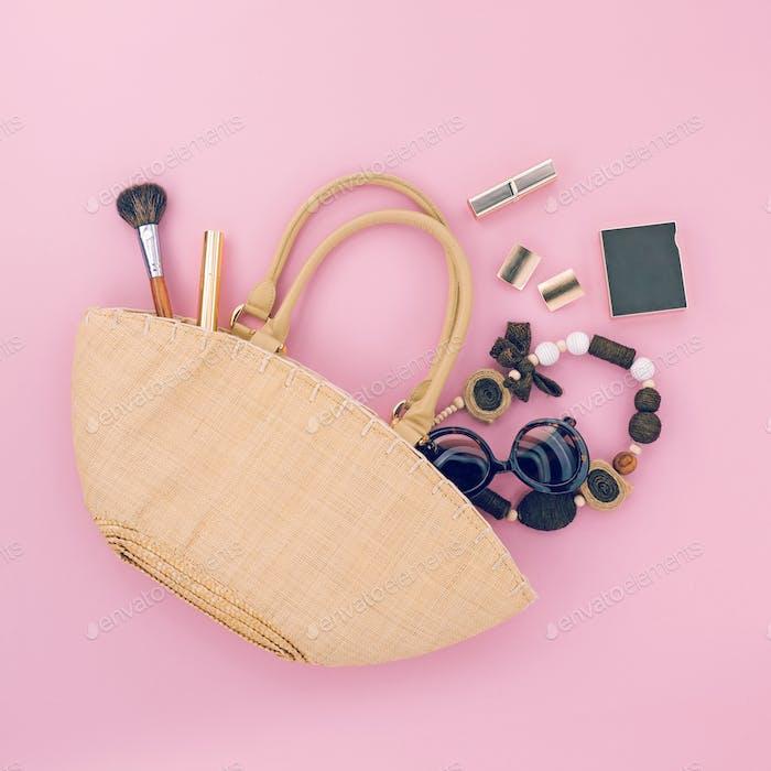 Handgefertigte Damen-Tasche mit verschiedenen Accessoires auf rosa Hintergrund