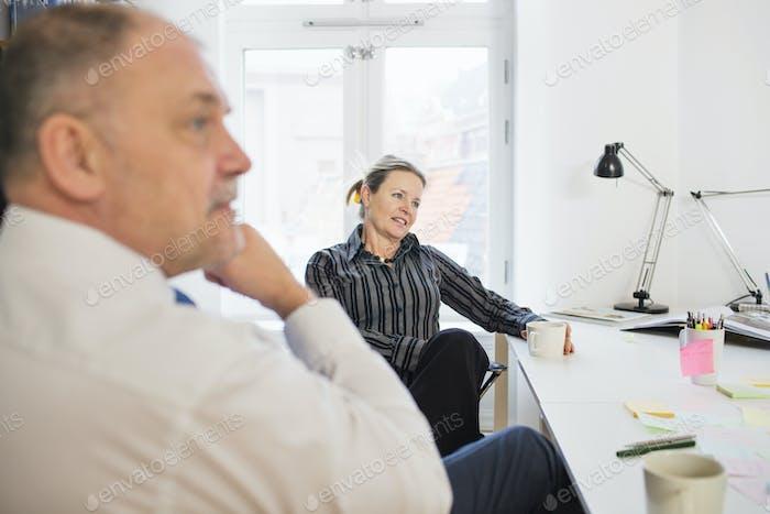 Personas de negocios maduras mirando hacia otro lado mientras se sienta en el escritorio en la oficina