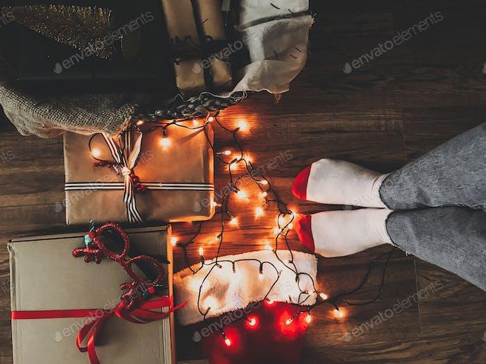 Christmas gift boxes, festive lights, santa hat and girl legs in cozy socks on wooden floor