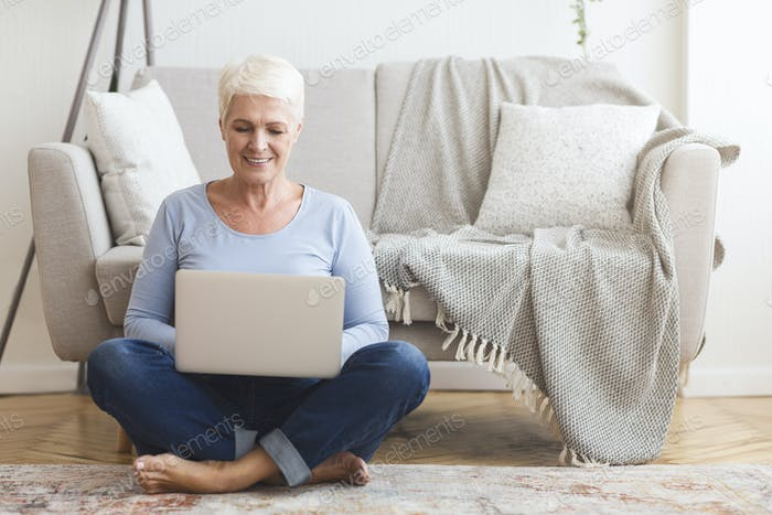 Resourceful mature woman sitting on floor and using laptop