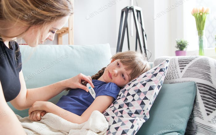 Sick little girl lying in bed mother checking her temperature