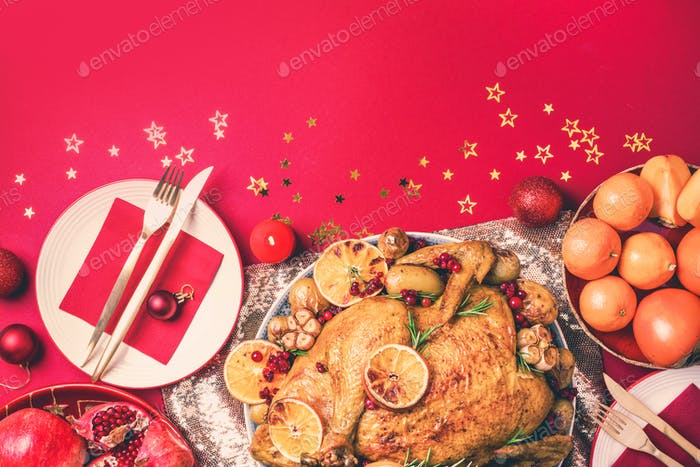 Roasted Christmas turkey with orange slices, cranberries, garlic with festive decoration, candles