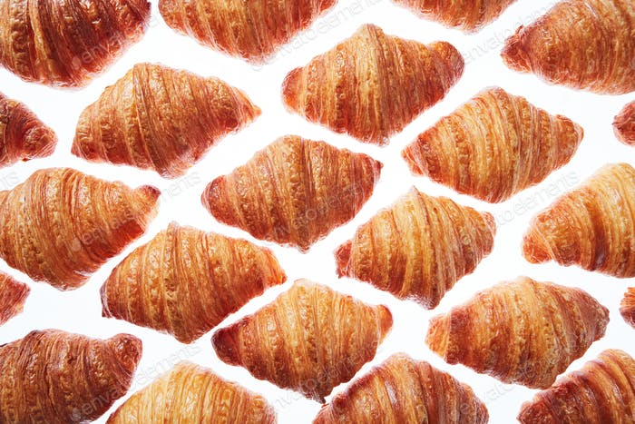 Pattern from freshly baked croissants on a white background
