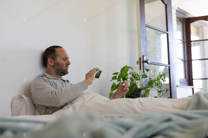 Sick Caucasian man self isolating and social distancing in quarantine lockdown during coronavirus co