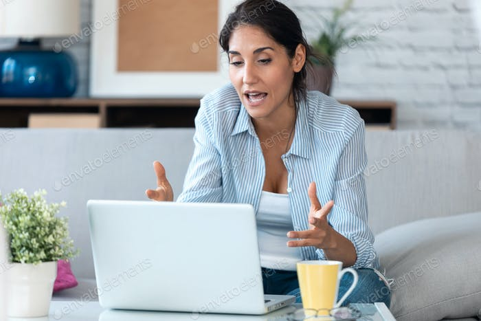 Business woman having online video call via laptop computer while working remotely from home.