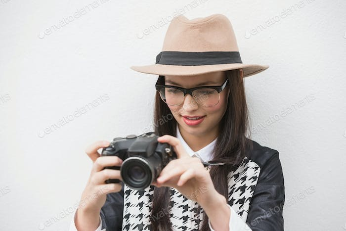 Pretty hipster looking at her camera against bleached wooden planks