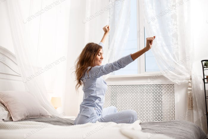 Brunette girl in the light-blue pajama stretches her arms up sitting on the canopy bed next to the