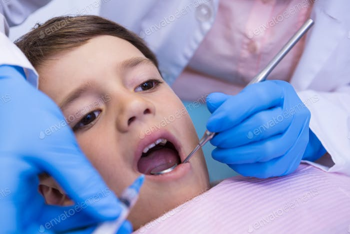 Cropped image of dentist examining boy