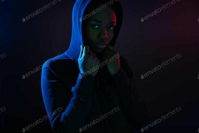 Dark colorful studio portrait of a cool black woman wearing hoodie