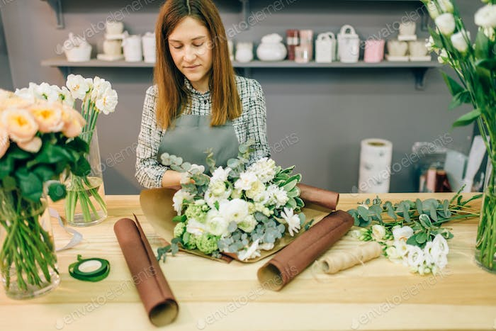 Female florist decorate fresh flower composition