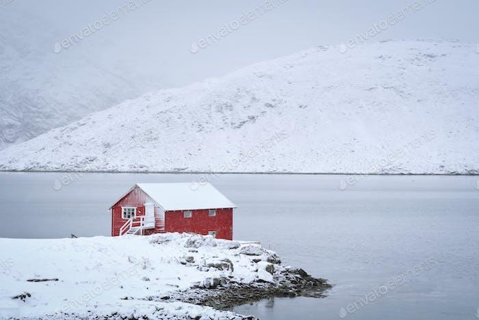 Red rorbu house in winter, Lofoten islands, Norway