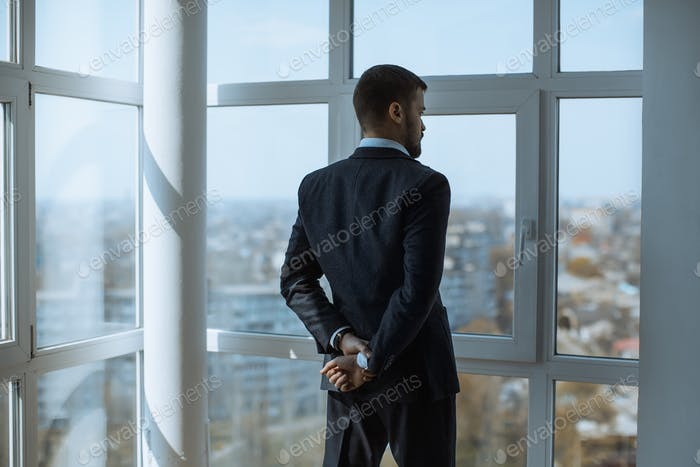 A Man in Suite at the Window