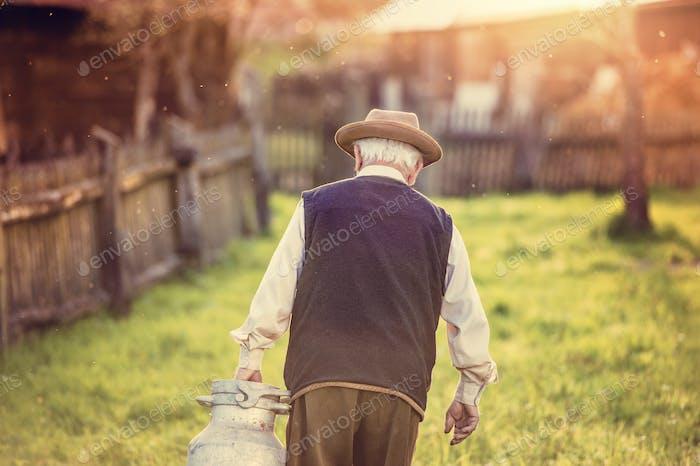 Senior Mann mit Milchkessel