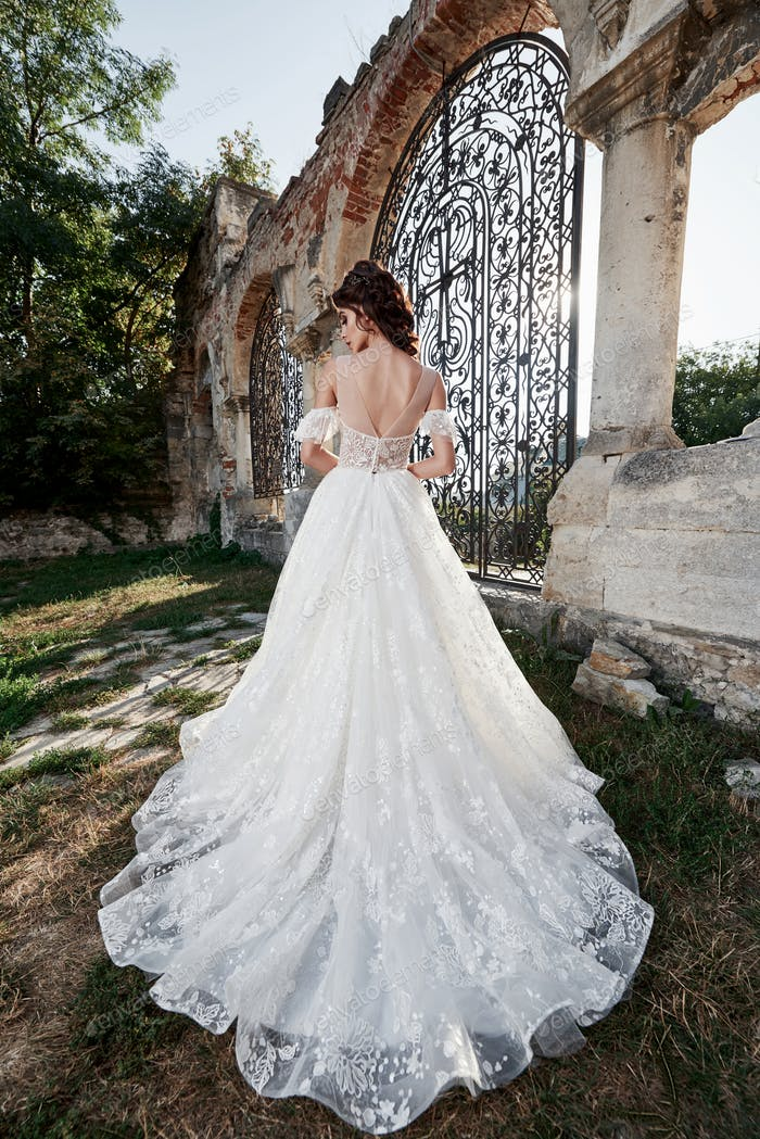 Beautiful bride in wedding dress, which is photographed on the wedding day near the old castle