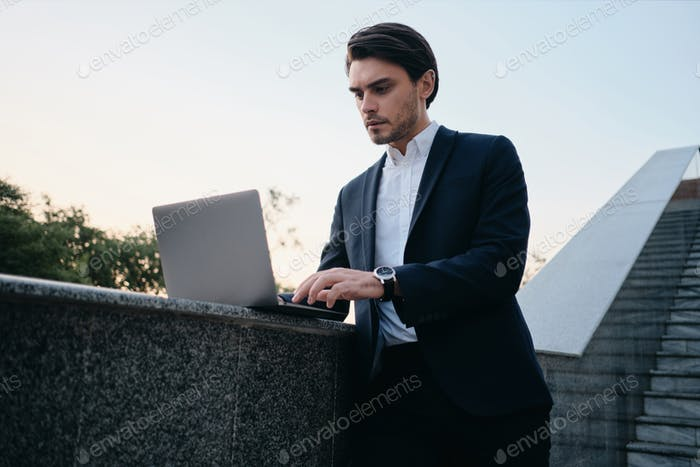 Young brunette man in white shirt and classic suit standing on stairs thoughtfully working on laptop
