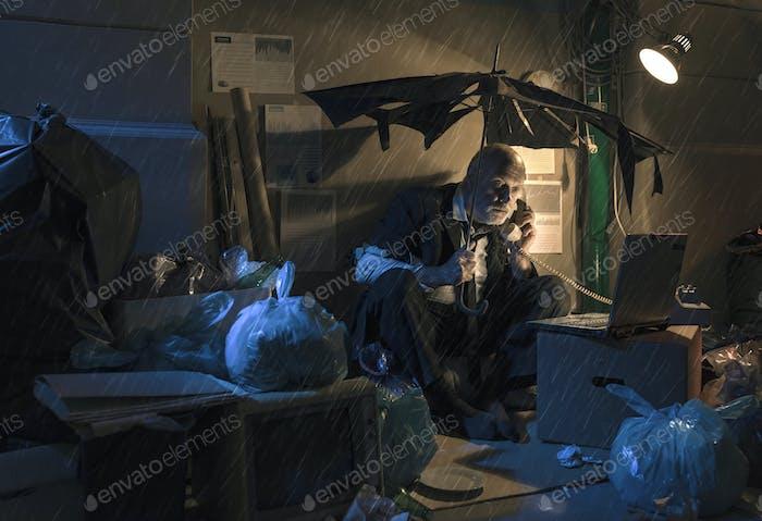 Broke jobless businessman sitting on the street under the rain