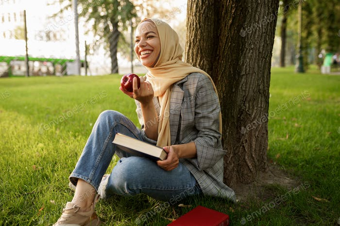 Arab girl in hijab holds apple and textbook