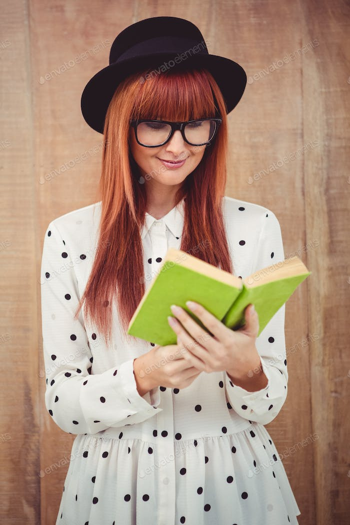 Hipster woman reading a green book against wooden background