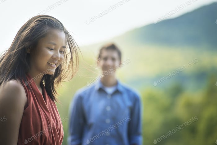 A young woman and young man outdoors.