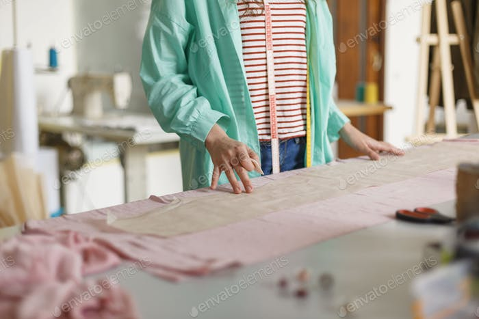 Close up tailor in colorful shirt and striped T-shirt drawing wi