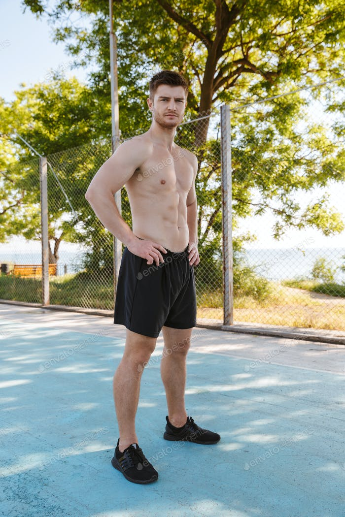 Confident shirtless sportsman in shorts standing