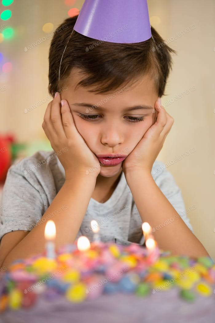 Upset boy sitting with birthday cake