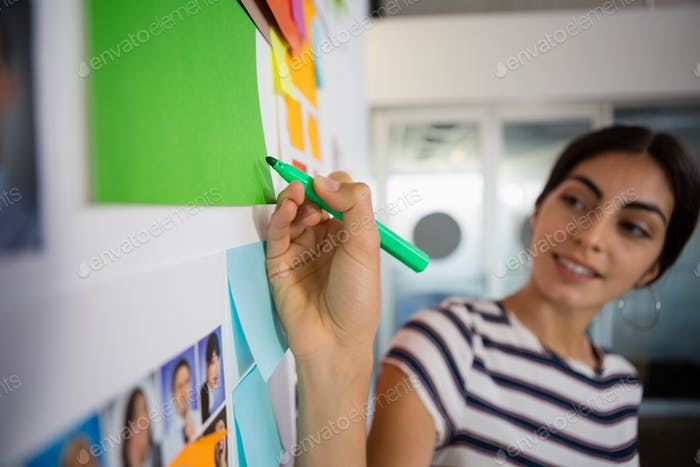 Young woman writing on sticky note at office
