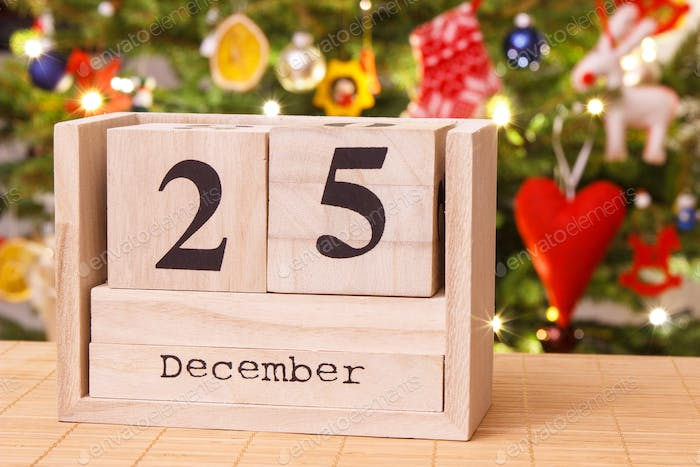 Date 25 December on calendar, festive tree with decoration in background,  Christmas time photo by ratmaner on Envato Elements