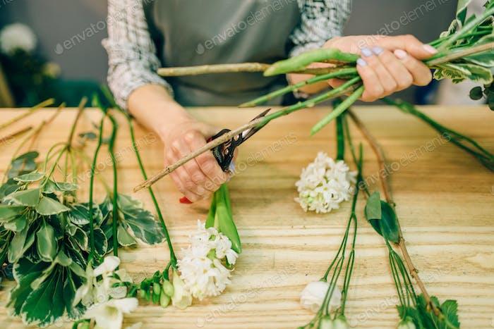 Weibliche Florist schneidet Rosen mit Gartenschere