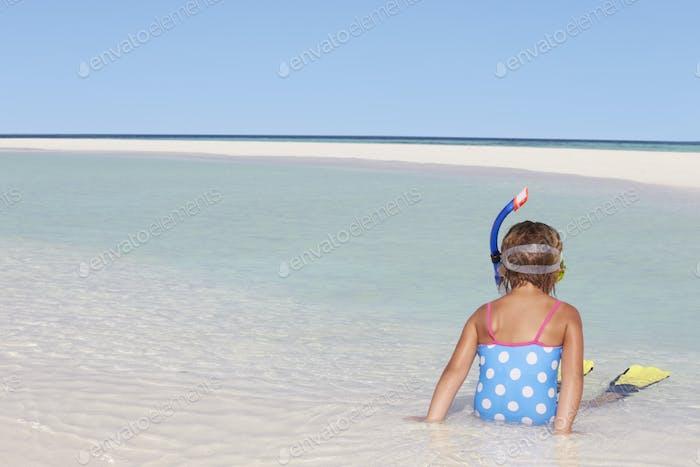 Mädchen sitzen am Strand tragen Schnorchel und Flossen