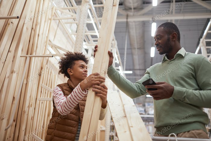 Father and Son Choosing Wooden Panels in Construction Store