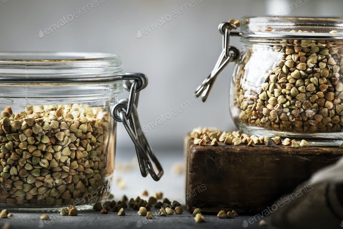 Uncooked green buckwheat groat in glass jar