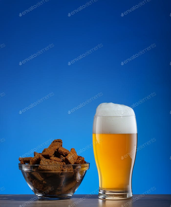 Glass of beer and rye crackers in plate on blue background