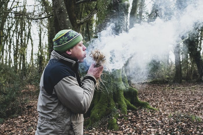 Man standing in a forest, blowing on bundle of straw, igniting fire.