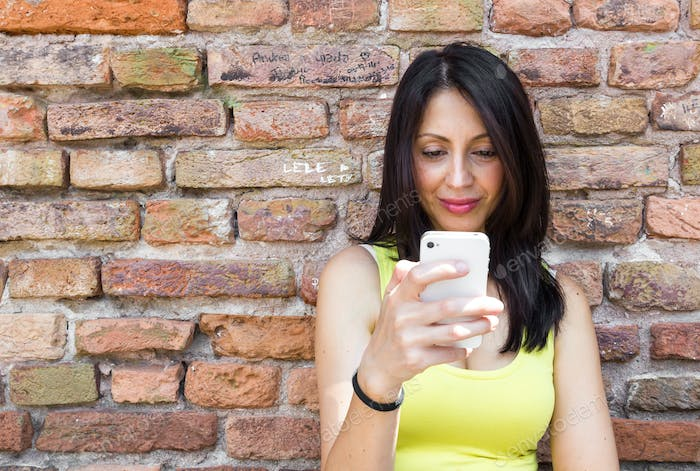 Young brunette woman looking at her smartphone.