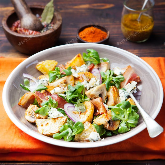 Potato salad with bacon, mushroom on orange napkin