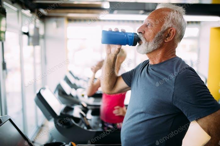 Senior Mann Trinkflasche Wasser auf Fadenmühle im Fitnessstudio