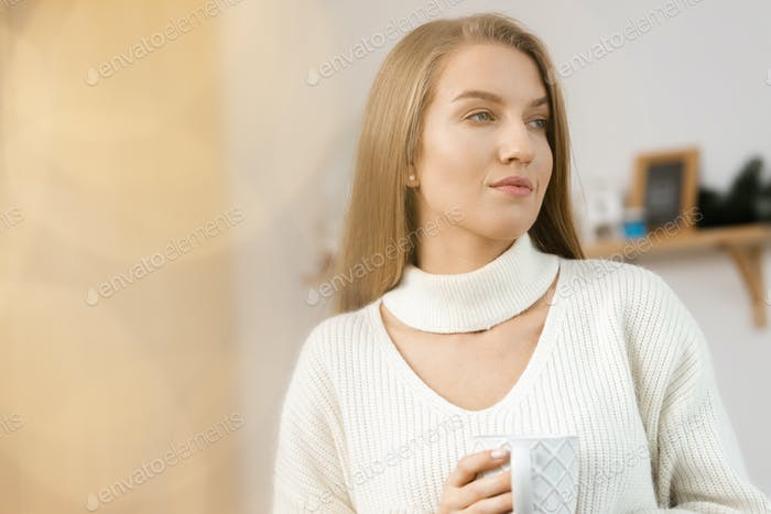 Young woman drinking hot beverage in kitchen