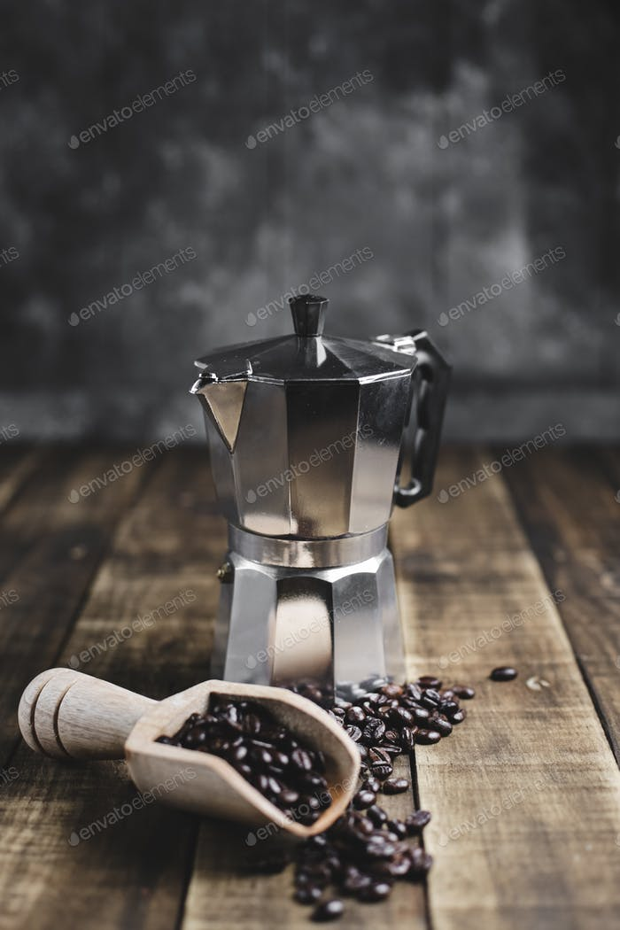coffee beans in wooden scoop and moka pot with wood background