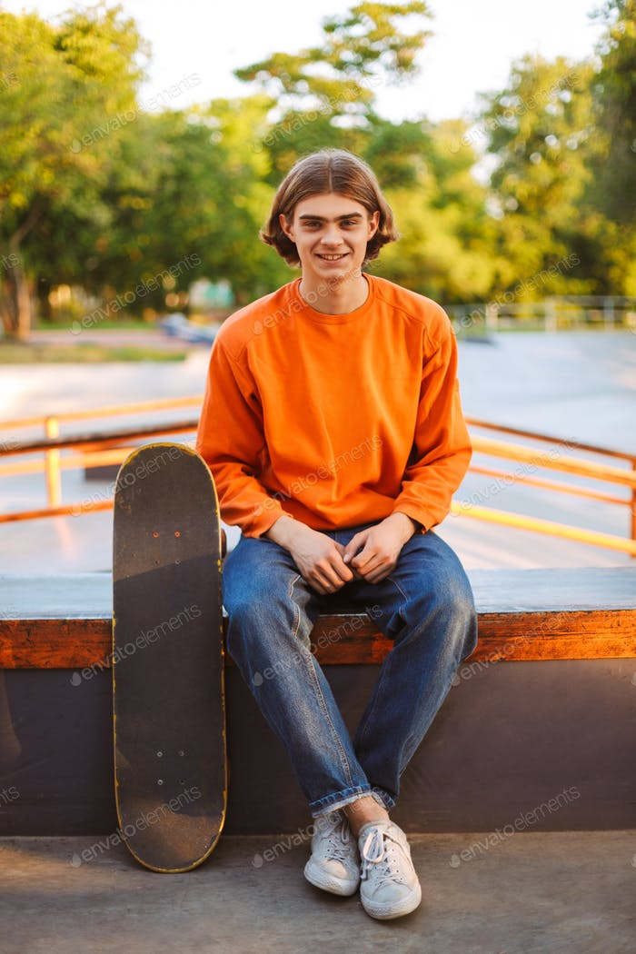 Young smiling skater in orange pullover and jeans happily lookin