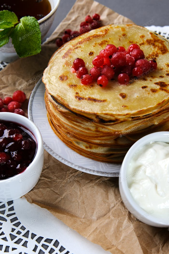 Stack of pancakes served with fresh cranberries, jam and cream o