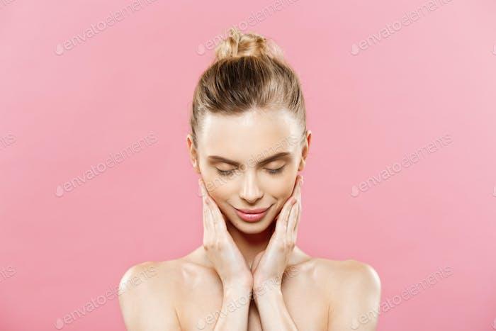 Beauty Concept - Schöne kaukasische Frau mit sauberer Haut, natürliches Make-up auf leuchtend rosa isoliert
