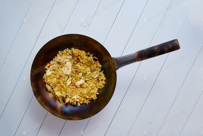 Delicioso plato tailandés en wok caliente. Pollo frito con arroz y verduras