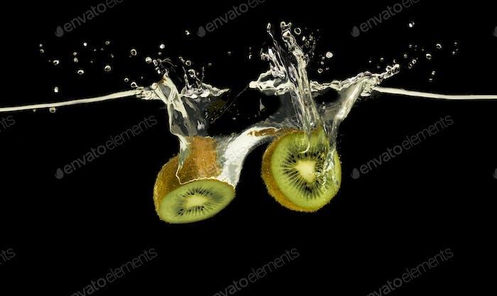 Fresh ripe kiwi halves falling in water