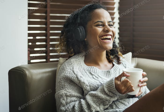 Woman enjoying music on her sofa