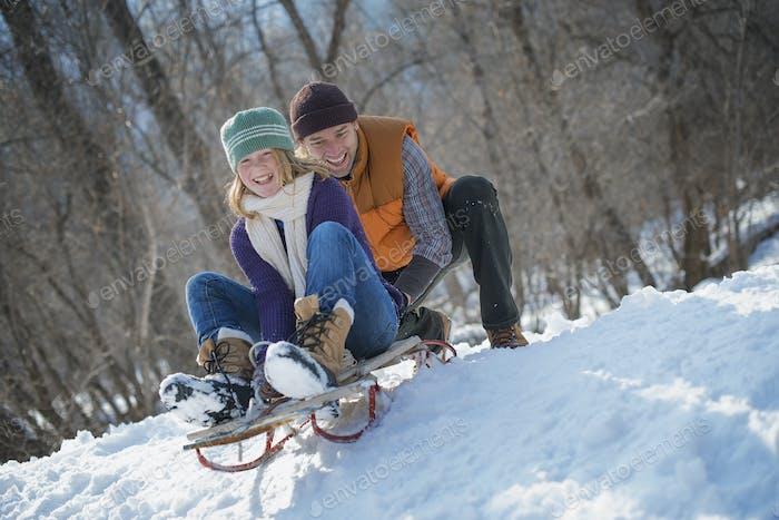 Winterlandschaft mit Schnee auf dem Boden, Mann schiebt eine junge Frau auf einer Rodel.