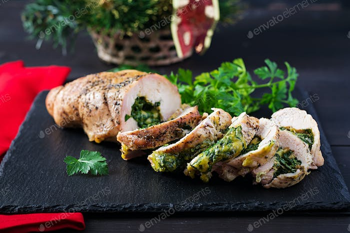Roasted sliced Christmas roll of turkey with spinach and cheese