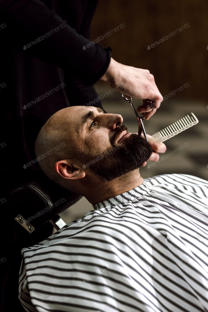 Men's fashion. The barber scissors beard of brutal man in the stylish barbershop