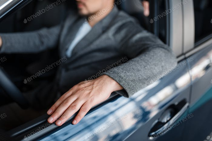 Male person sitting in new car, showroom